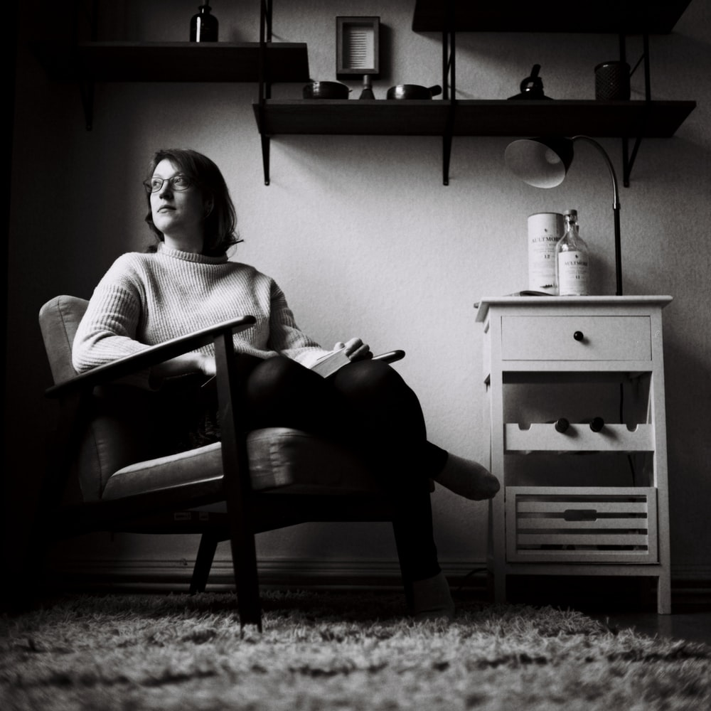 woman in white sweater sitting on chair