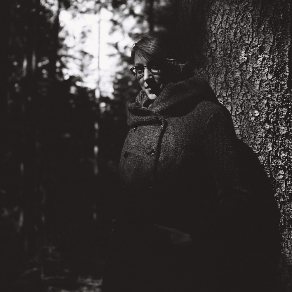 grayscale photo of woman in black coat