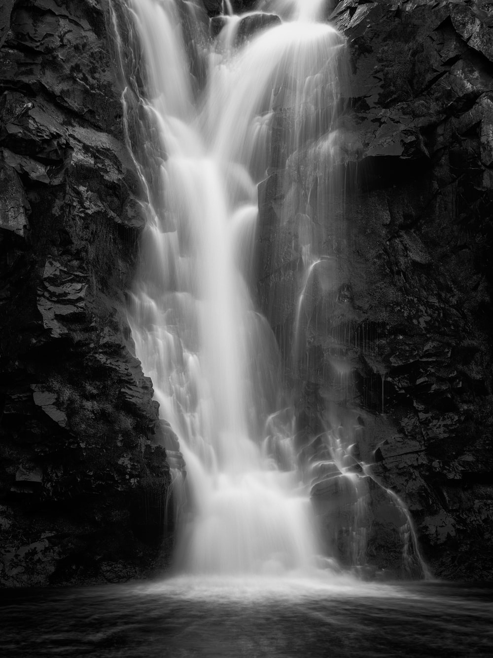 grayscale photo of waterfalls during daytime