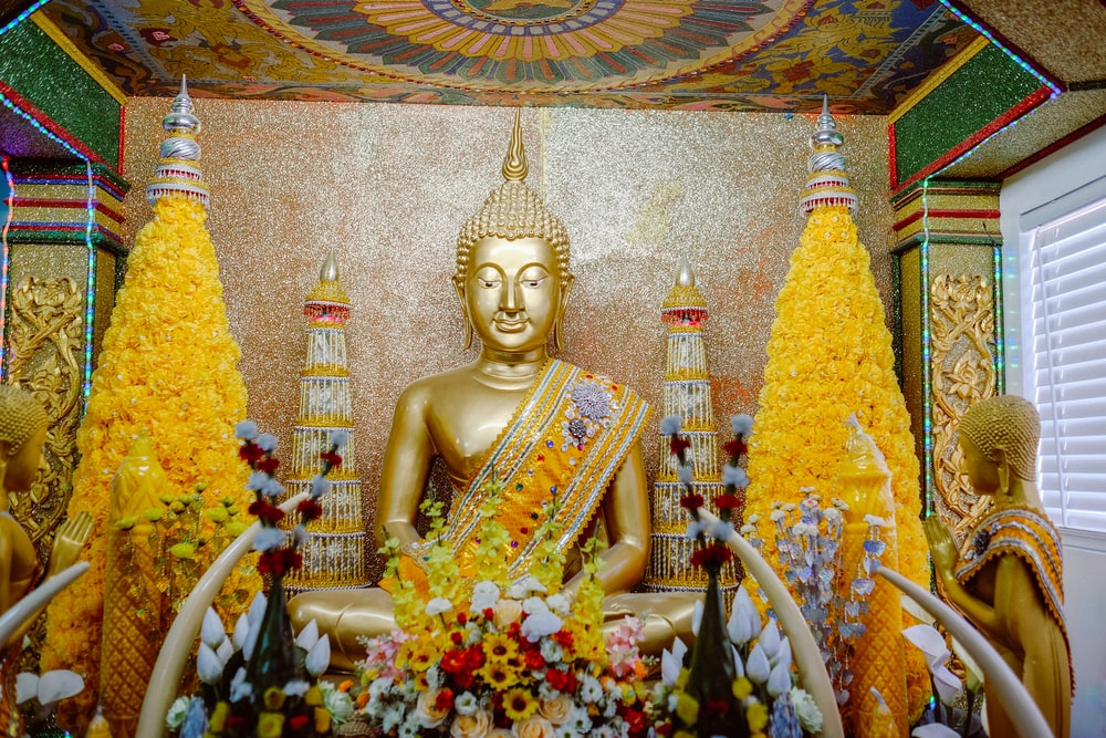 gold buddha statue surrounded by flowers