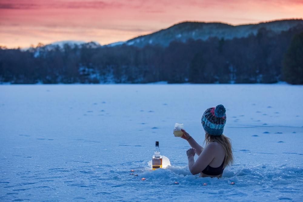 woman in black bikini top holding clear plastic bottle on water
