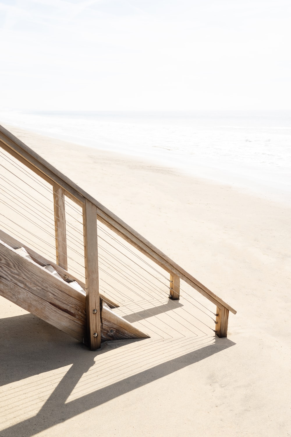 brown wooden staircase on white sand beach during daytime