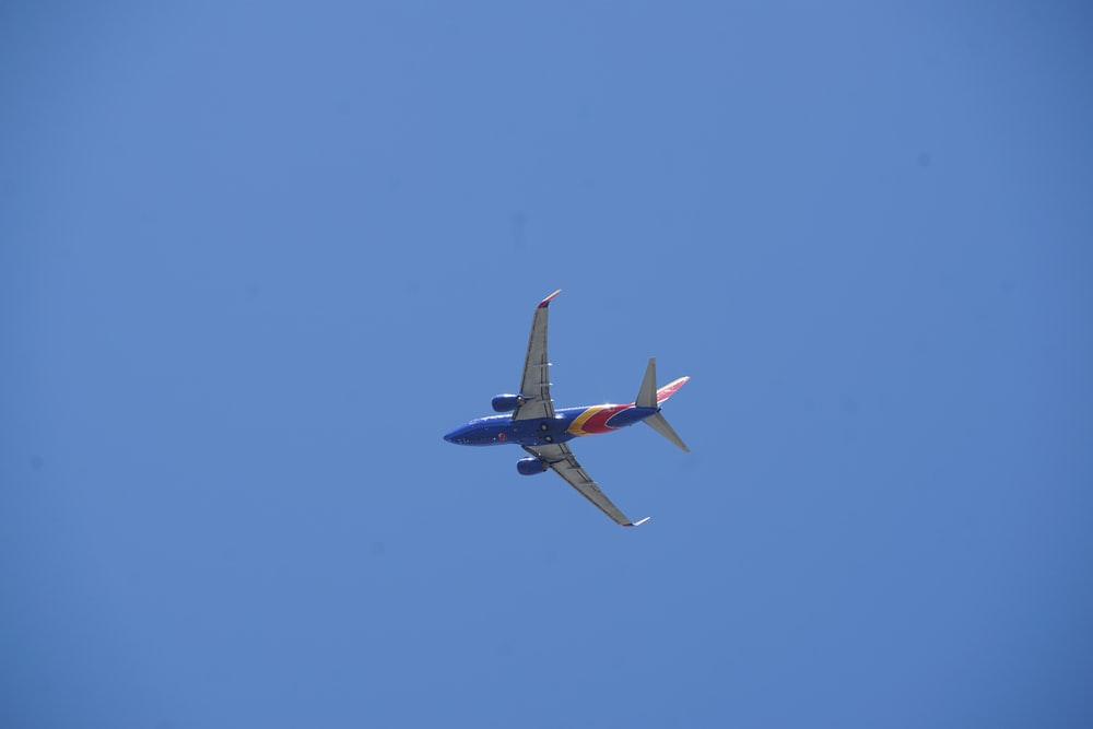 red and white airplane in mid air during daytime
