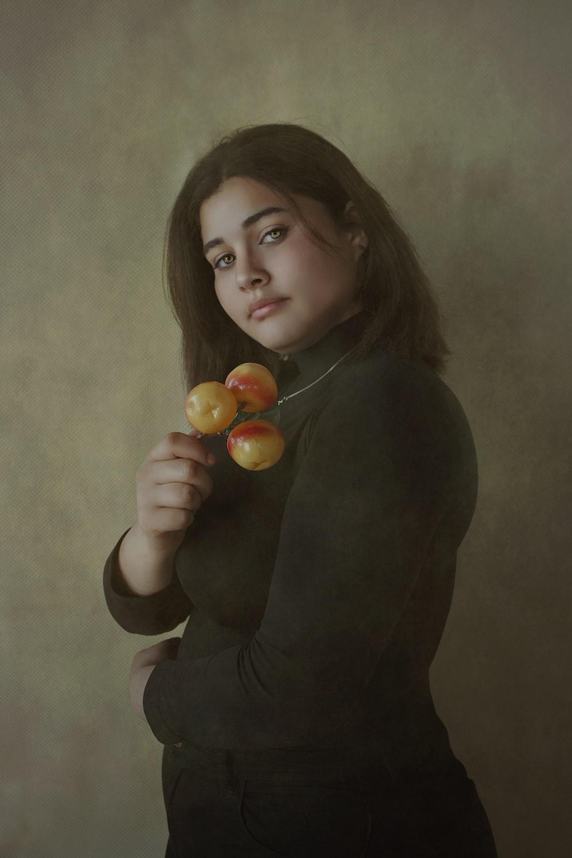 woman in black long sleeve shirt holding orange fruit