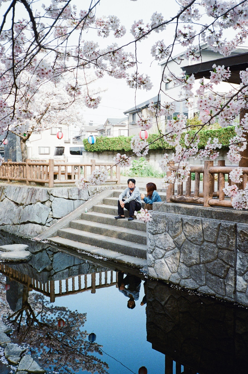 man and woman sitting on concrete bench near body of water during daytime
