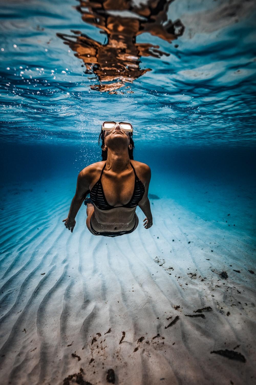 woman in black bikini lying on the water
