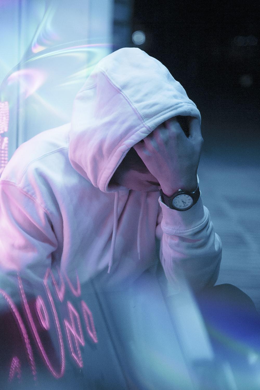 man in white hoodie wearing black round analog watch