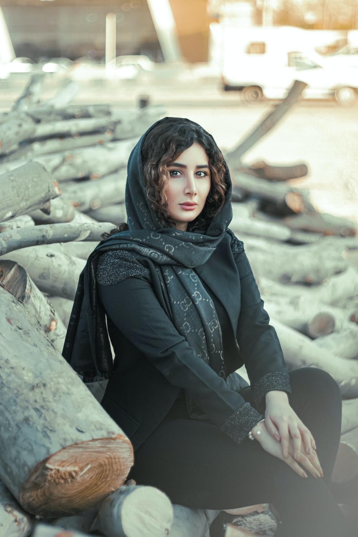 woman in black hijab sitting on rock during daytime