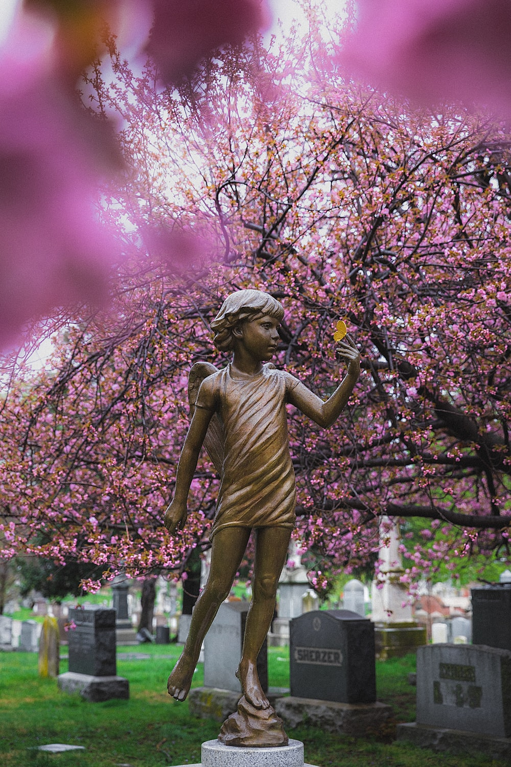 woman in green dress statue under pink leaf tree during daytime