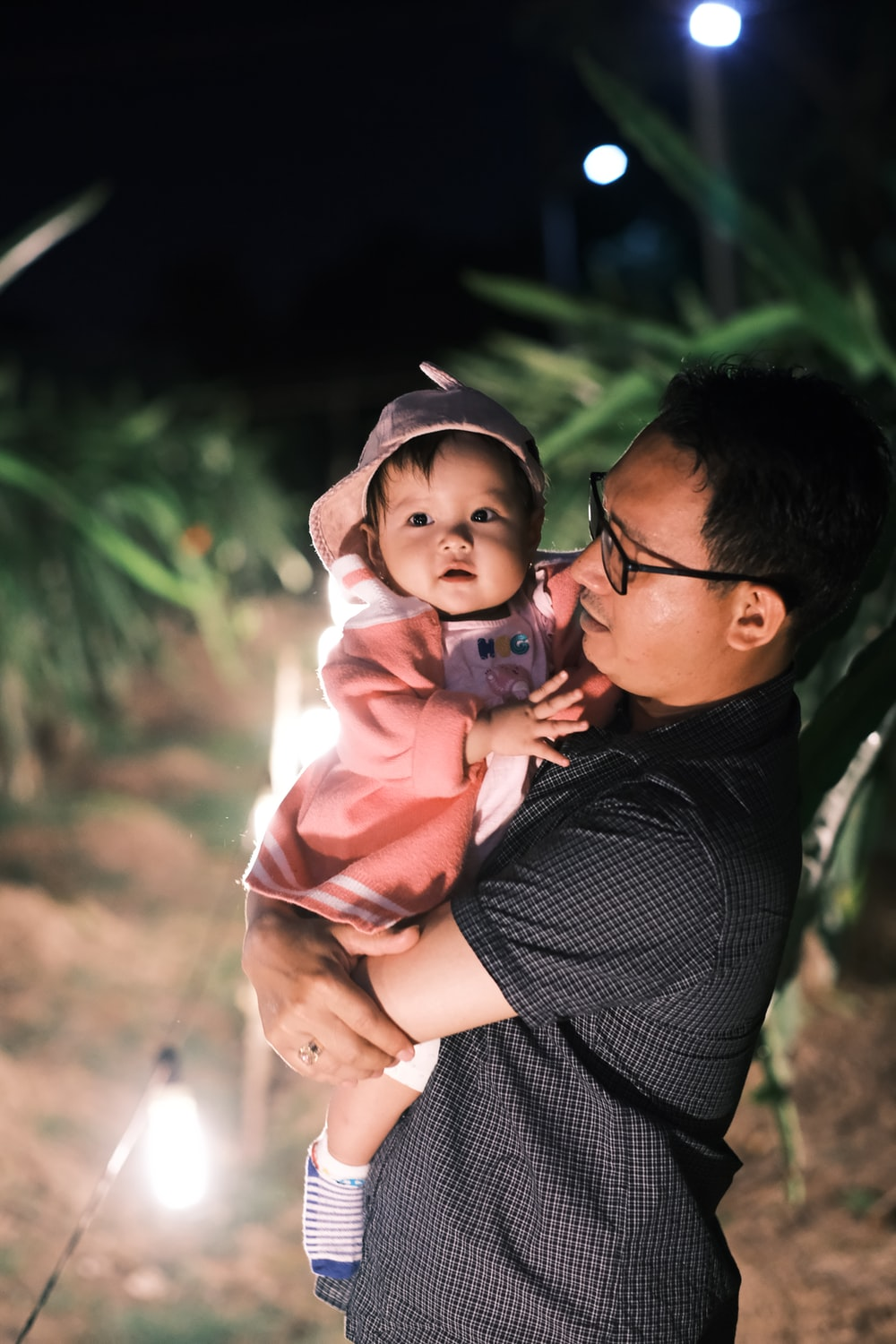 man in black and white pinstripe dress shirt carrying baby in pink hoodie