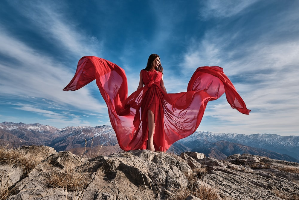 woman in red dress sitting on brown rock under blue sky during daytime