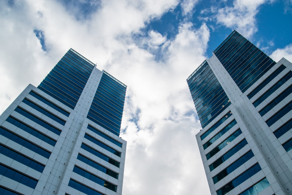 low angle photography of high rise building under white clouds during daytime