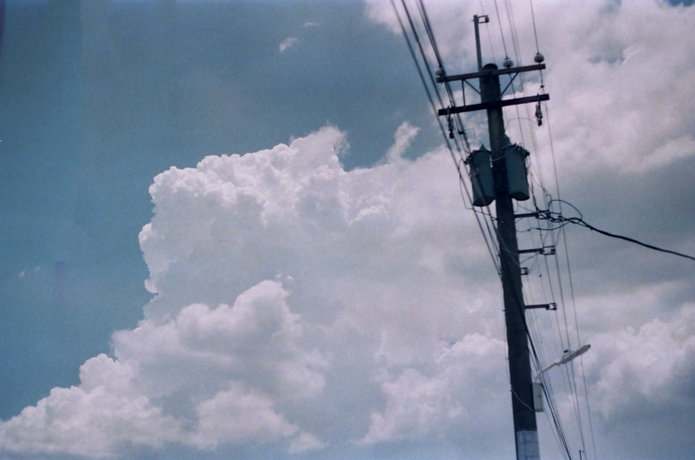 black electric post under white clouds and blue sky during daytime