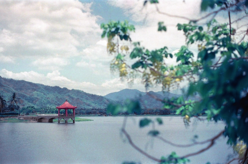 red wooden house on lake near green trees and mountain during daytime
