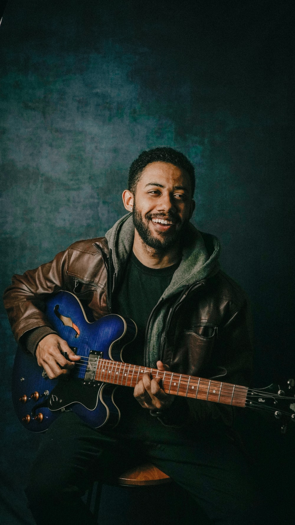 man in black leather jacket playing blue electric guitar