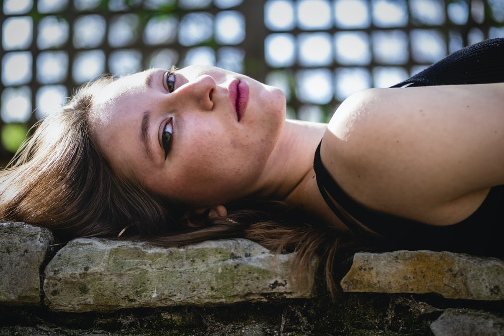 woman in black tank top lying on brown wooden plank