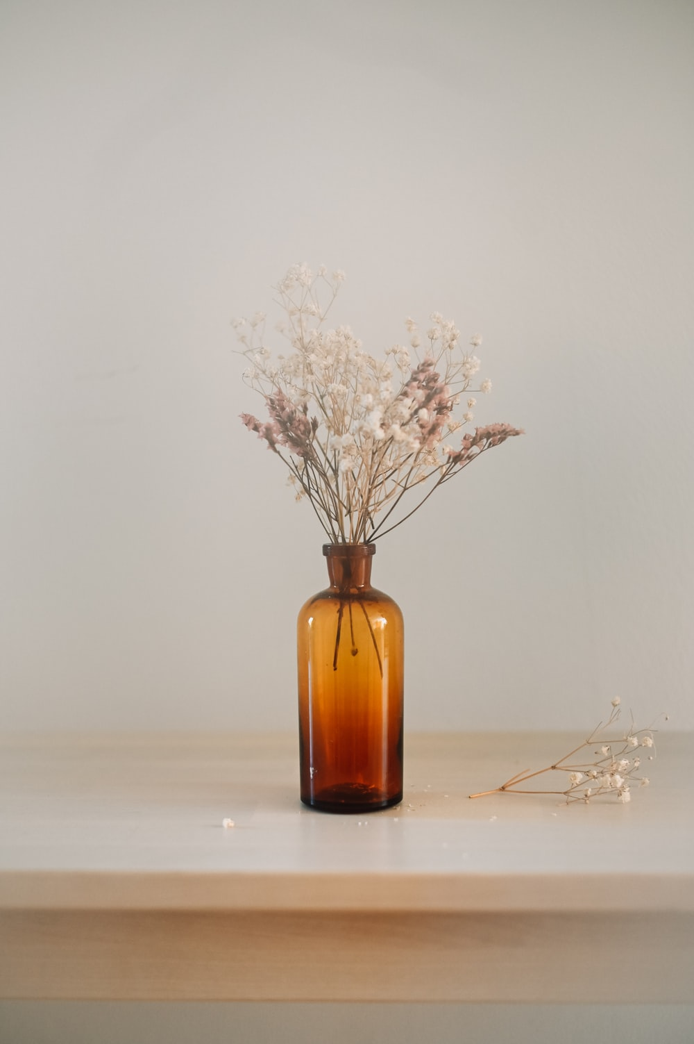 white flowers in brown glass bottle