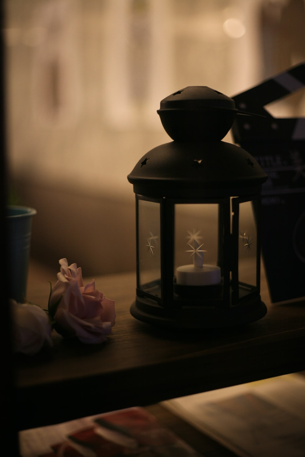 black candle lantern on brown wooden table