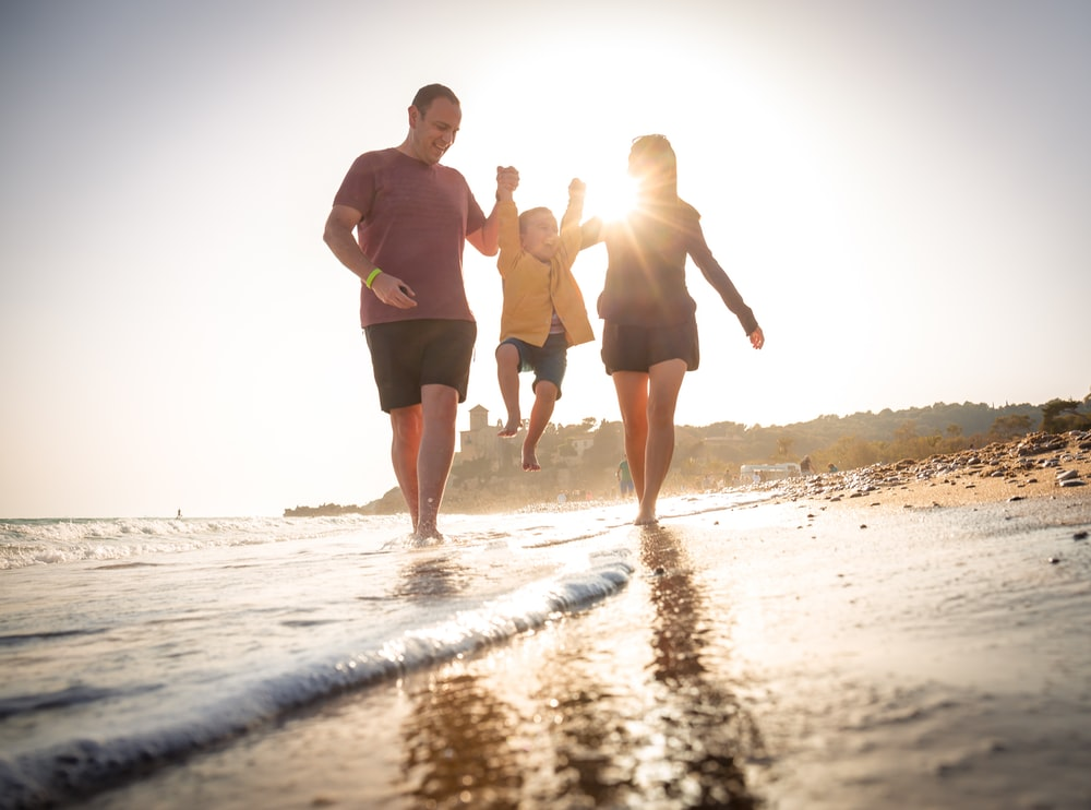 2 men and woman walking on beach during daytime