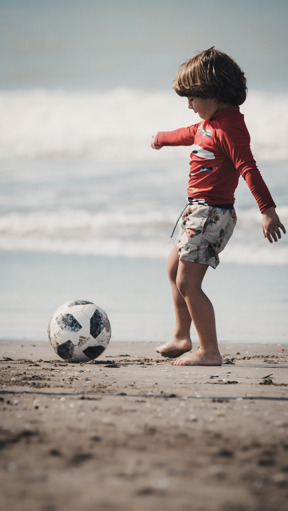 woman in red long sleeve shirt and white skirt holding soccer ball on beach during daytime