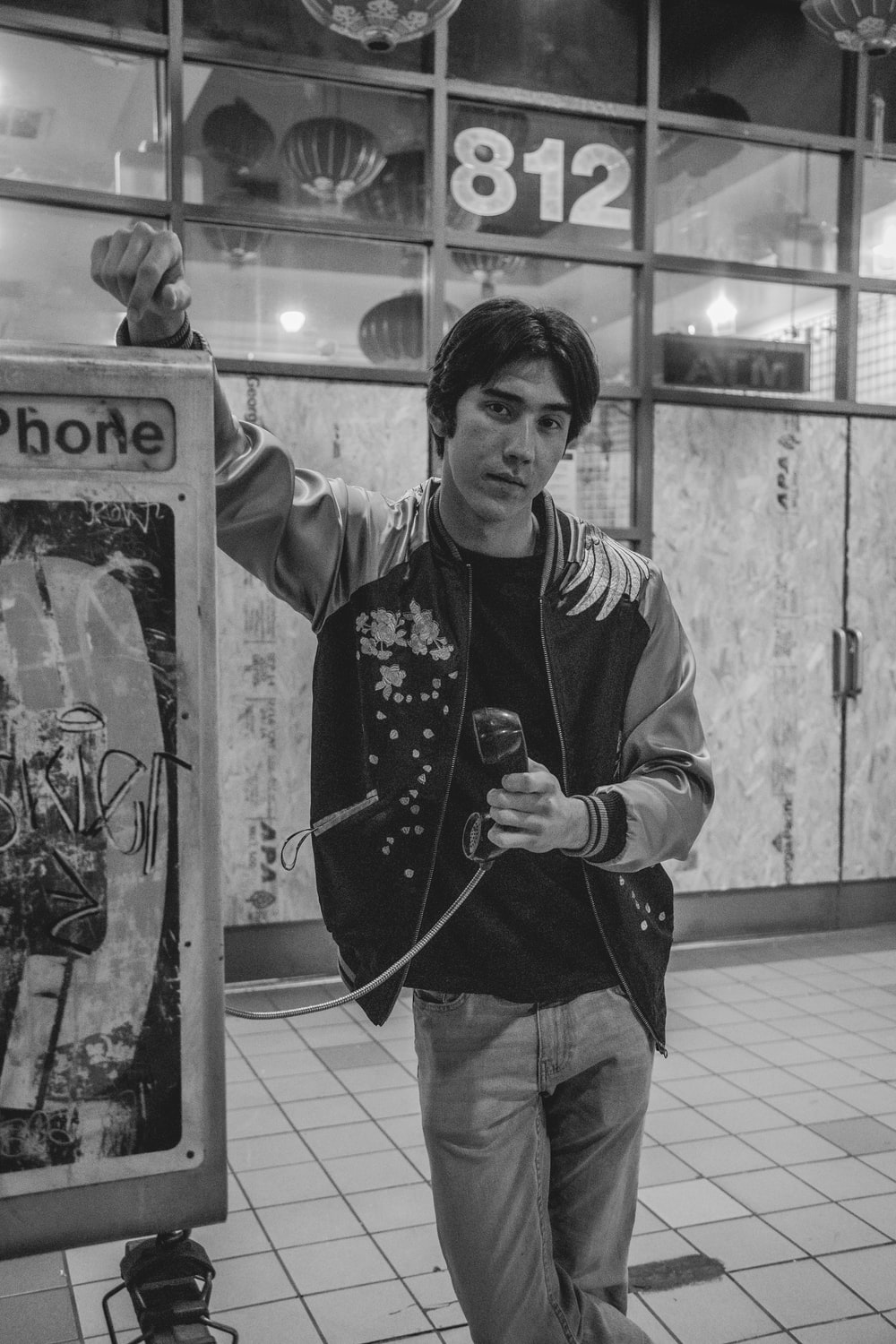 grayscale photo of man in zip up jacket holding telephone