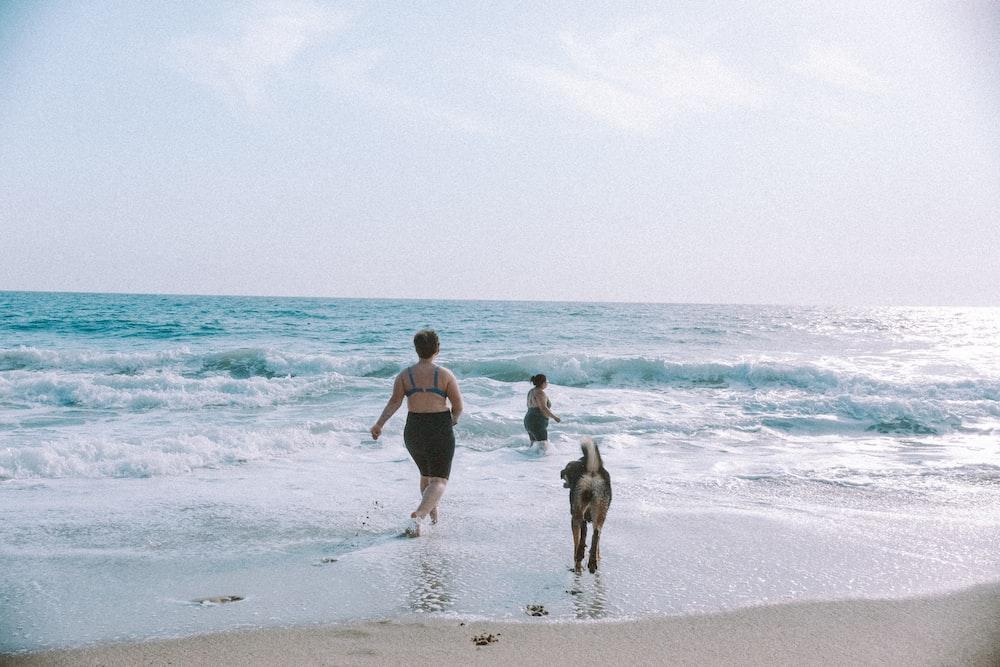 woman in black bikini walking on beach with dog during daytime