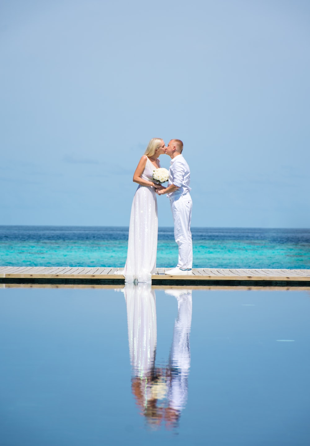 couple kissing on beach during daytime