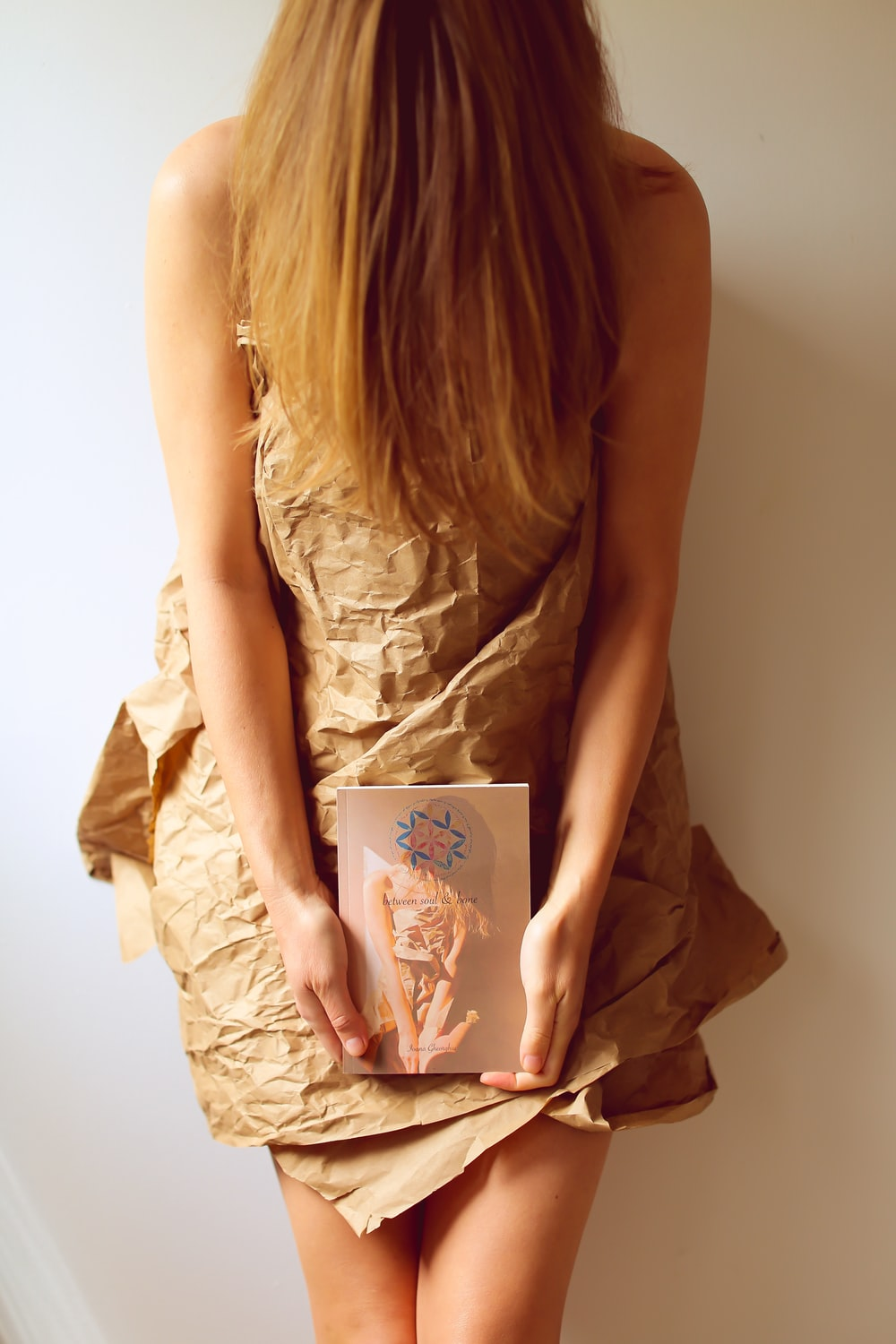woman in brown dress holding book