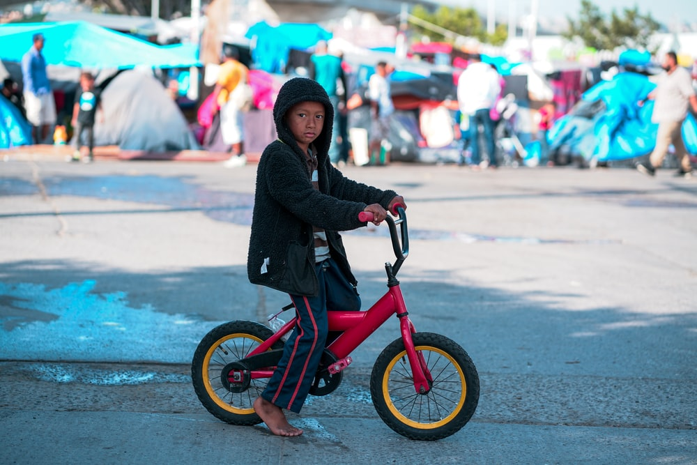 woman in black jacket riding red bicycle during daytime