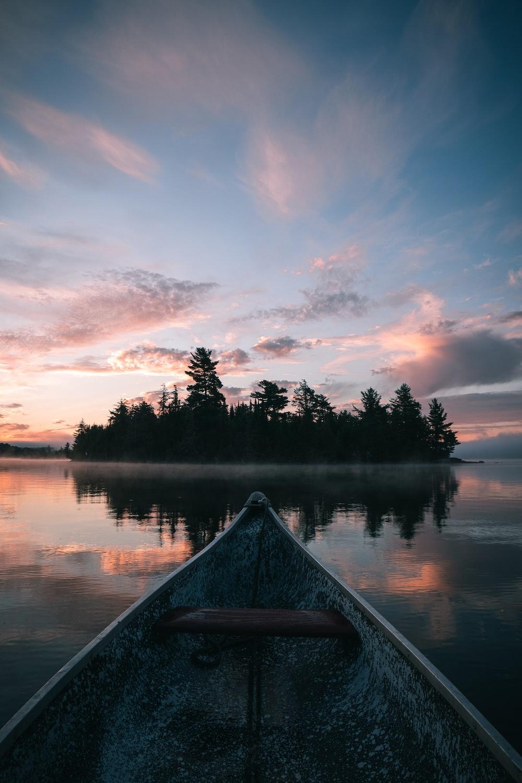 brown canoe on lake during sunset