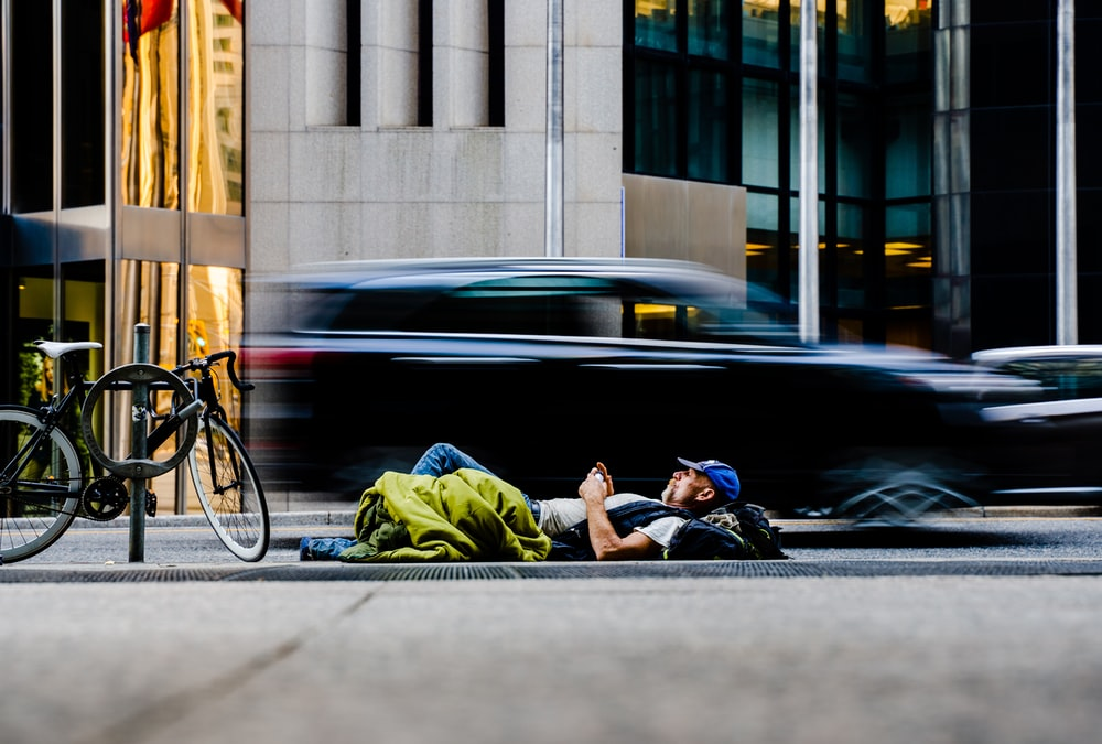 man in green jacket sitting on black road bike near black car during daytime