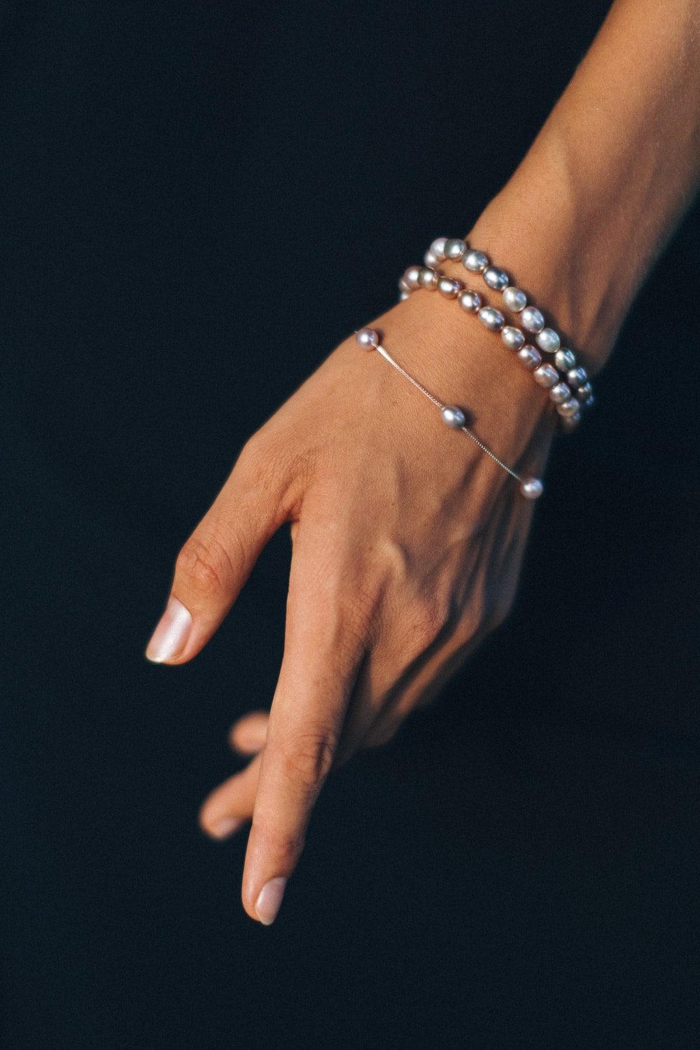person wearing silver bracelet and gold ring