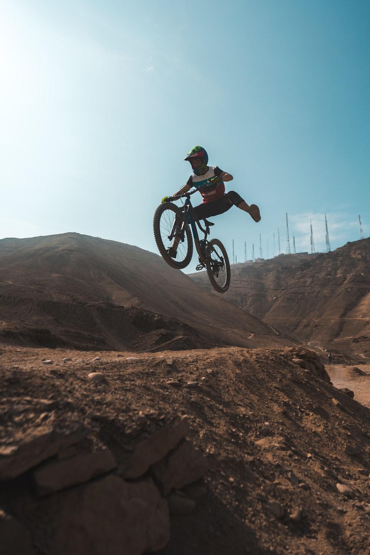 man in black jacket riding bicycle on brown mountain during daytime