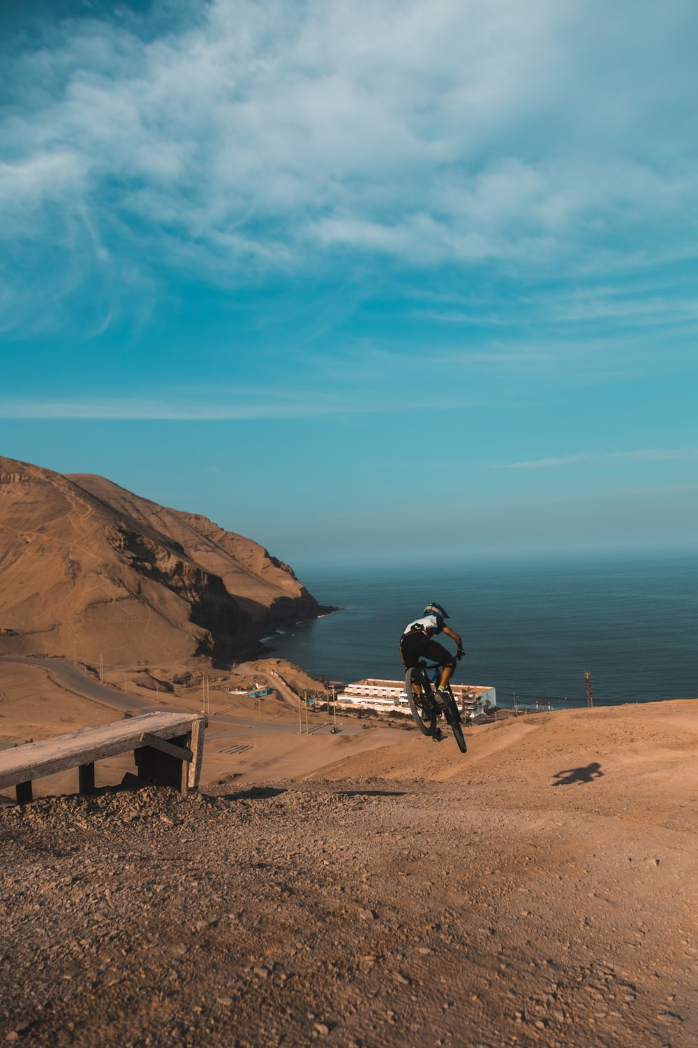 man in black shirt riding bicycle on brown sand near body of water during daytime
