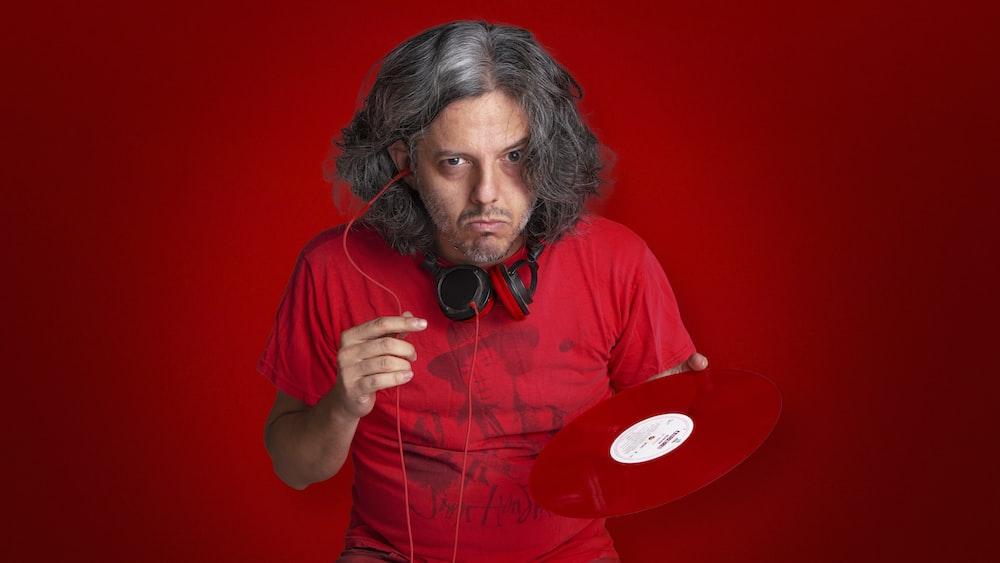 man in red crew neck t-shirt wearing black headphones