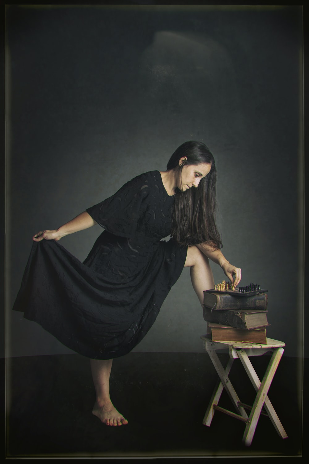 woman in black dress sitting on brown wooden seat