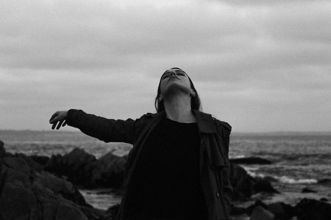 Grayscale Photo of Woman In Black Jacket Standing On Rock Formation Near Sea - unsplash