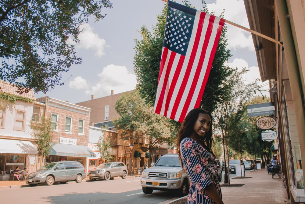 woman holding us a flag standing on road during daytime