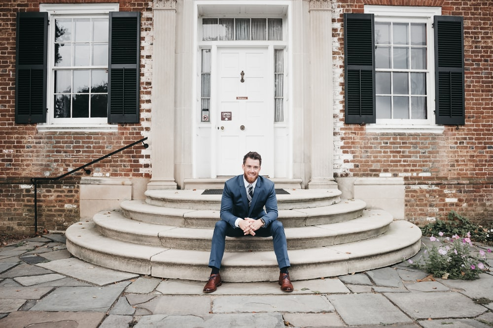 man in blue suit sitting on brown concrete stairs