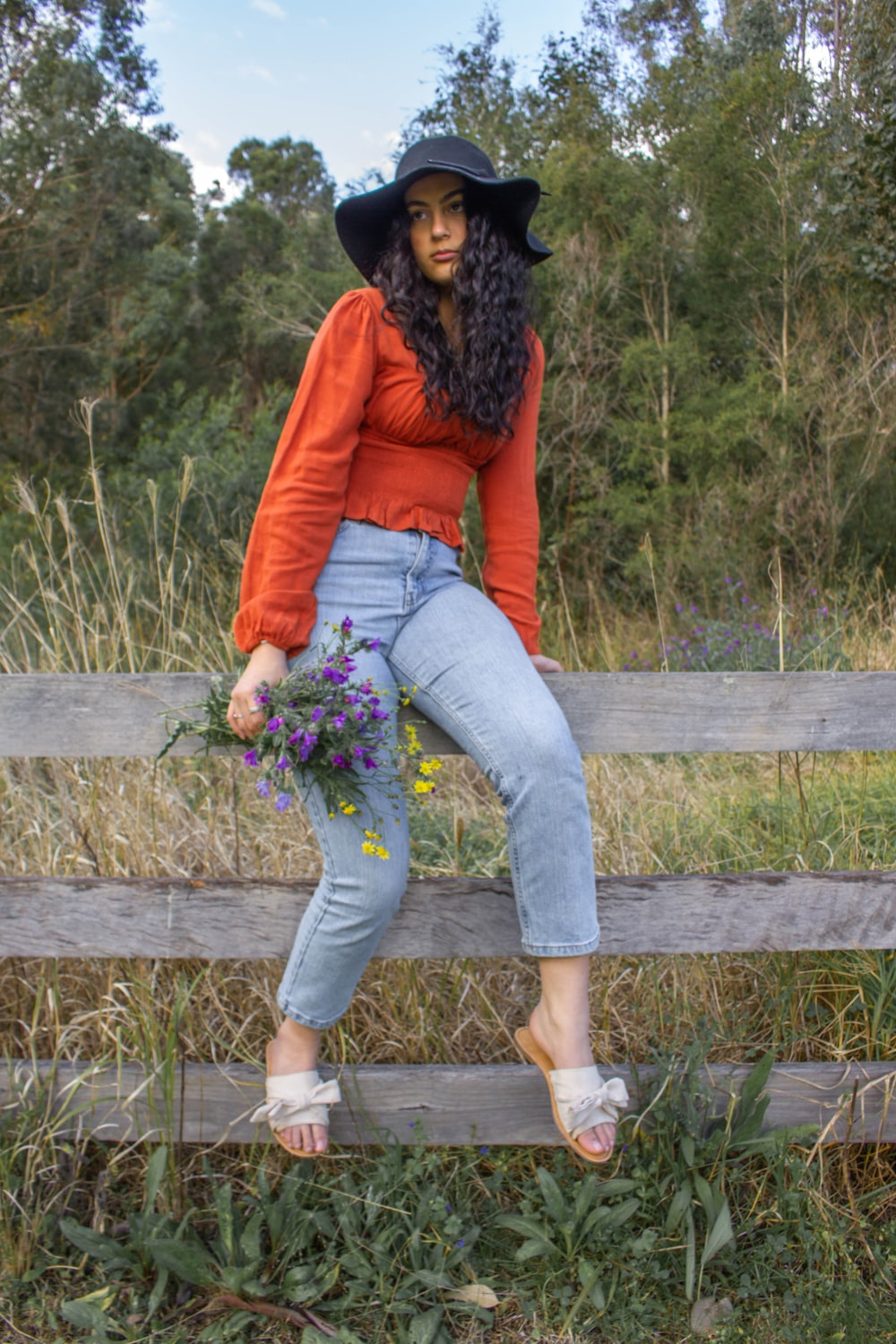 woman in red long sleeve shirt and blue denim jeans sitting on brown wooden fence during