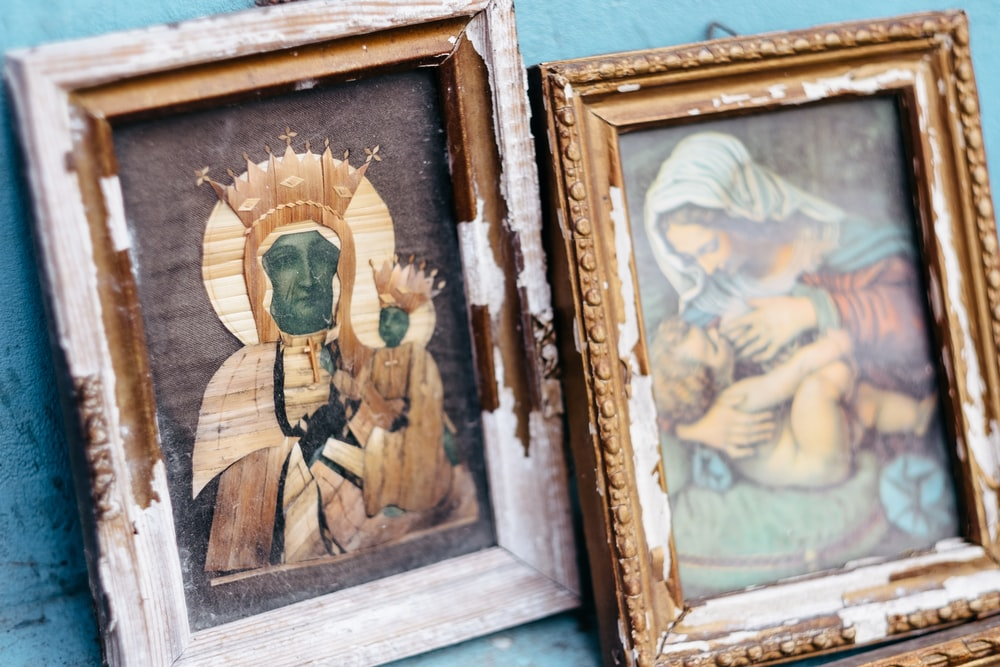 brown wooden framed painting of man and woman