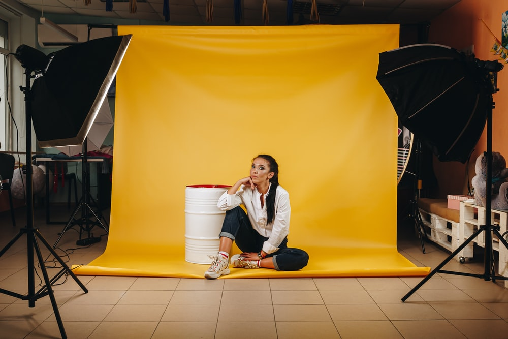 woman in white long sleeve shirt sitting on yellow floor tiles
