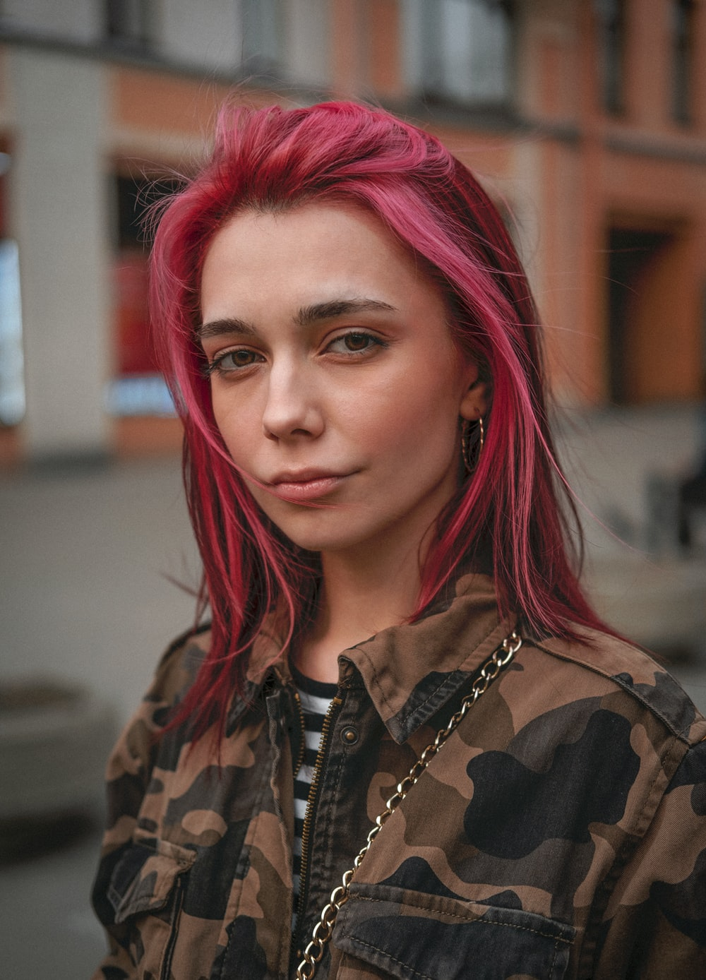 woman in black and brown camouflage shirt with pink hair