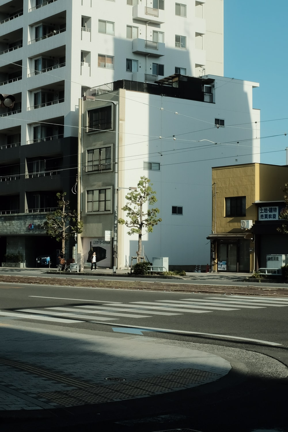 white and black concrete building beside road during daytime