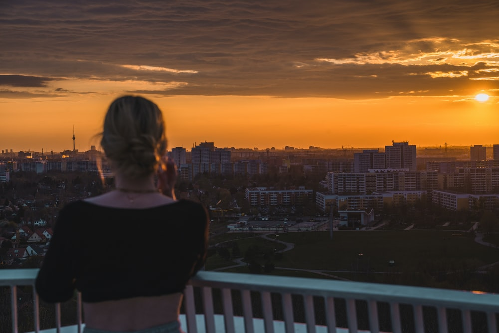 woman in black shirt standing on balcony during sunset