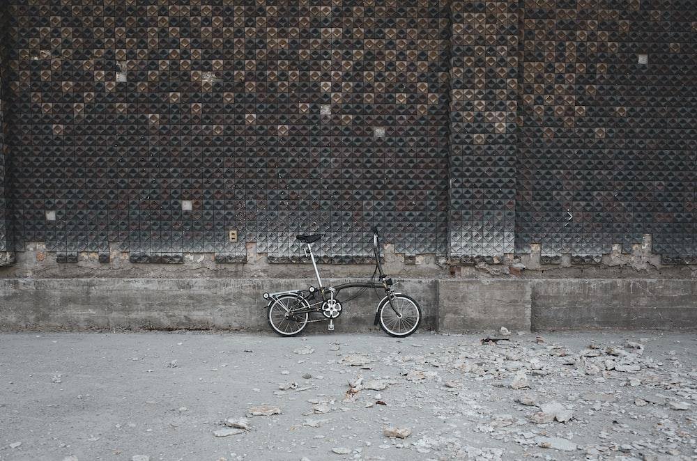 black bicycle on brown brick wall