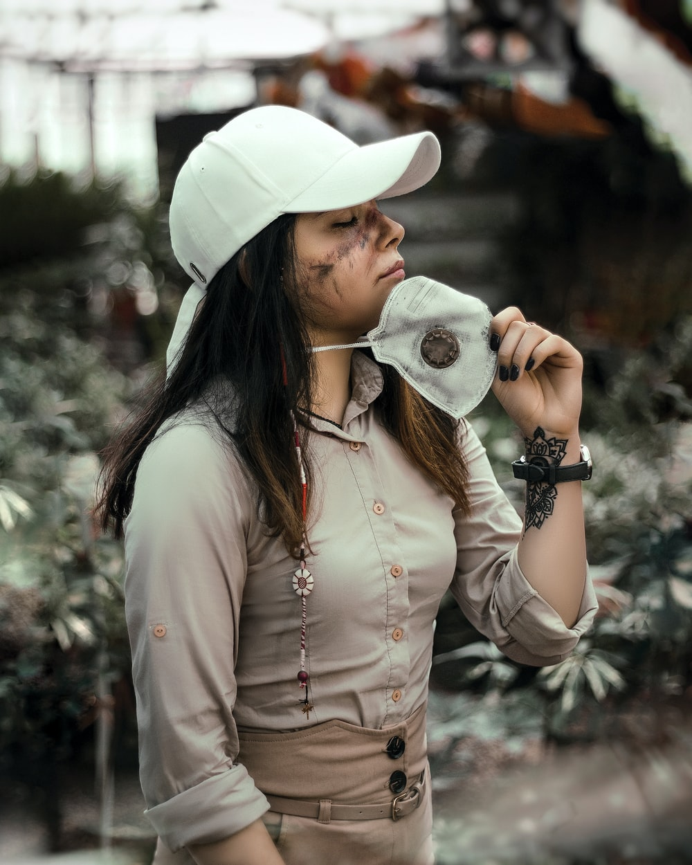 woman in white hat and white long sleeve shirt holding black and white camera