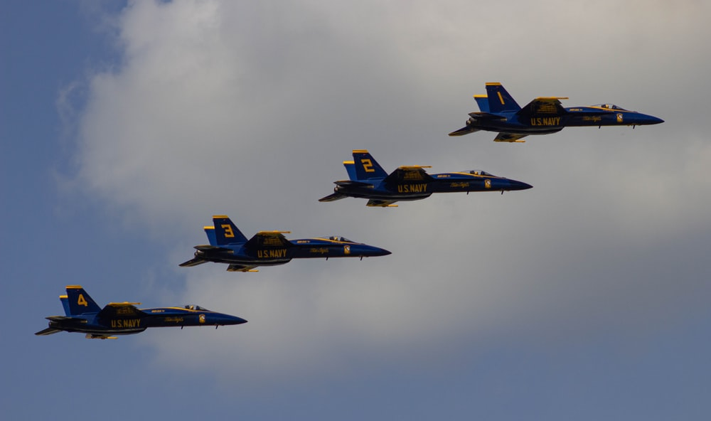 blue and yellow fighter plane on mid air during daytime