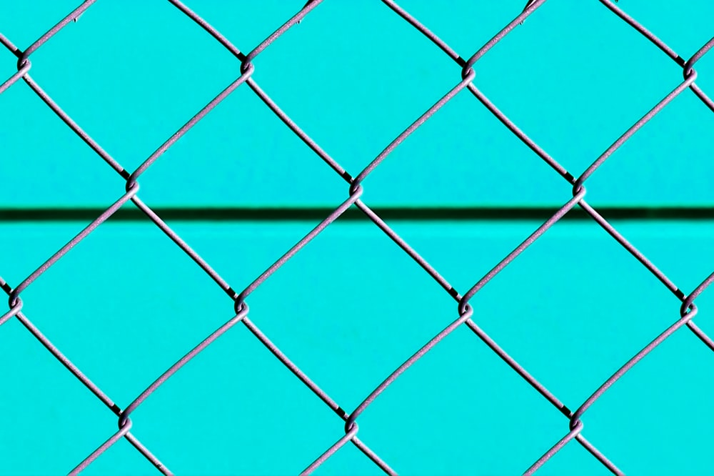 blue metal fence with chain link fence