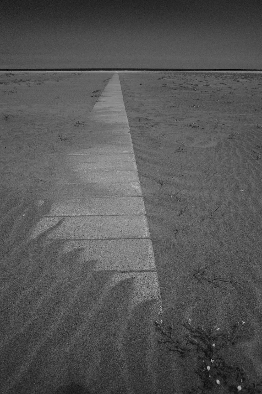 grayscale photo of concrete pavement